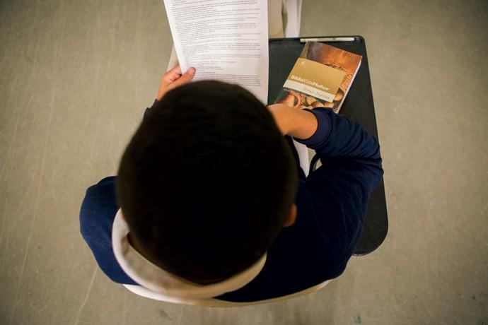 À direita, jovem lê texto em reforço escolar. Diferentemente das prisões, os centros de medidas socioeducativas são um local para completar o ensino formal, fazer cursos profissionalizantes e participar de oficinas artísticas   (Foto: Marcelo Min)