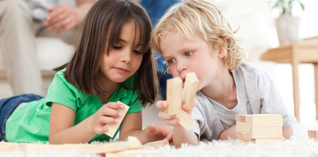 Menino e menina brincando juntos no chão (Foto: Shutterstock)