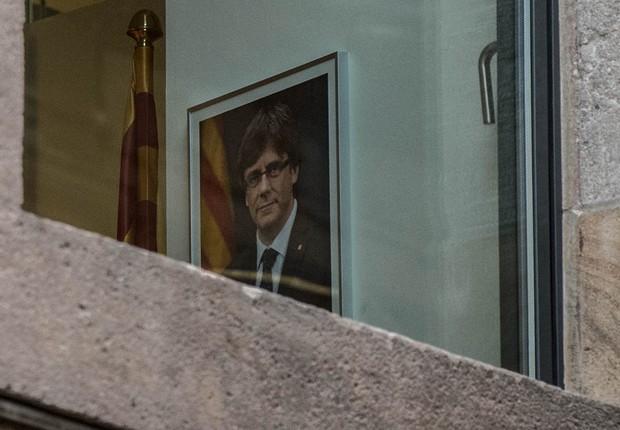 Retrato do presidente deposto da Catalunha, Carles Puigdemont, é visto da janela da sede do governo catalão após o governo central de Madri tomar controle da região (Foto: David Ramos/Getty Images)