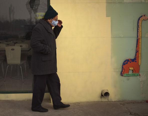 Homem usa máscara para ir à rua em Pequim por conta do alto nível de poluição. (Foto: Alexander F. Yuan/AP Photo)