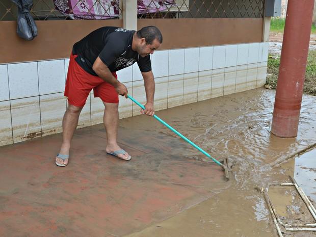José Dairton tira a lama de dentro da casa da mãe com um rodo de limpeza (Foto: Aline Nascimento/G1)