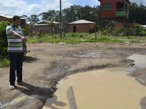 Comerciante Lindemberg Silva diz que poças de lama são comuns no bairro (Foto: Abinoan Santiago/G1)