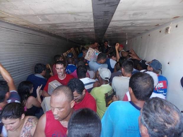 Pessoas se aglomeram no baú do caminhão para pegar carne (Foto: Rafael Machi / Diário de Penápolis)