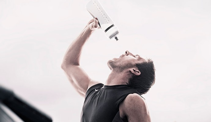 Homem após corrida bebendo água com squeeze (Foto: Getty Images)