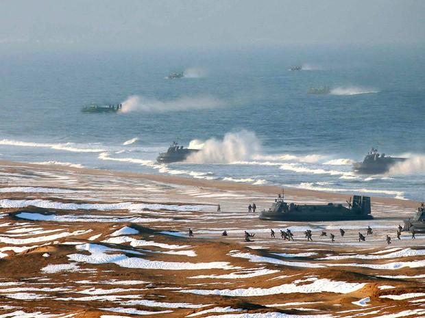 Tropas norte-coreanas fazem treinamento de chegada e defesa de costa em praia não identificada do país. Em meio ao momento de tensão internacional, o país colocou suas tropas em posição de combate, com armas apontadas para alvos americanos. (Foto: AFP/KCNA)