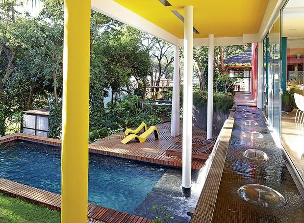 O arquiteto Leo Romano manteve as árvores no terreno em declive e projetou o paisagismo com plantas tropicais e espelho-d'água com queda para a piscina. Assim, as áreas internas e externas parecem se confundir (Foto: Victor Affaro/Casa e Jardim)