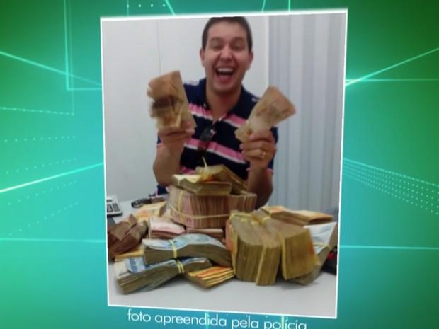 Foto mostra o funcionário da Coaf, Carlos Luciano Lopes, segurança maços de dinheiro que, segundo polícia, seria propina (Foto: TV Globo/Reprodução)
