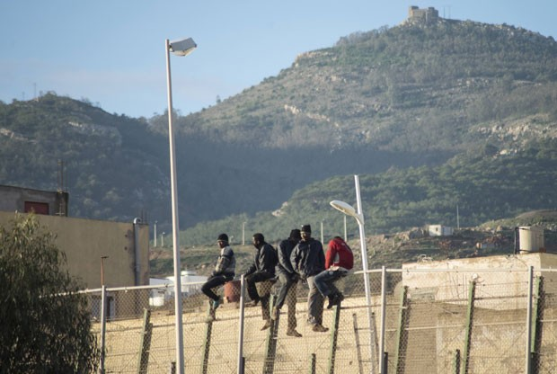 Imigrantes africanos são vistos no topo da cerca na fronteira entre o enclave espanhol de Melilla e o Marrocos nesta terça-feira (30) (Foto: Jesus Blasco de Avellaneda/Reuters)