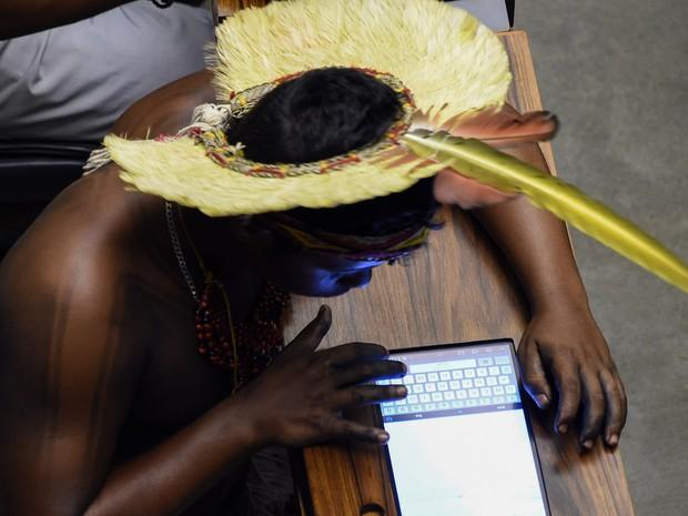 Um índio utiliza um tablet durante sessão especial em homenagem aos povos indígenas no Congresso Nacional, em Brasília. Os índios presentes no plenário protestaram contra PEC que altera demarcação de terras  (Foto: Evaristo Sa/AFP)