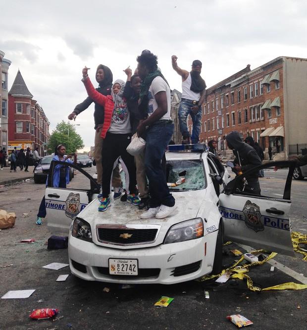 Pessoas sobem em carro da polícia em Baltimore nesta segunda-feira, durante protesto contra morte de jovem negro  (Foto: AP Photo/Juliet Linderman)