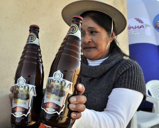 Uma mulher da comunidade indígena Aymara comercializa cerveja feita com quinoa, uma planta tradicional no país, em Challapata, no Sul da Bolívia, em imagem da quarta-feira (11) (Foto: Aizar Raldes/AFP)