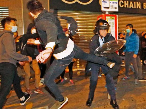 Manifestante salta para chutar um policial em Hong Kong (Foto: Kin Cheung / AP Photo)
