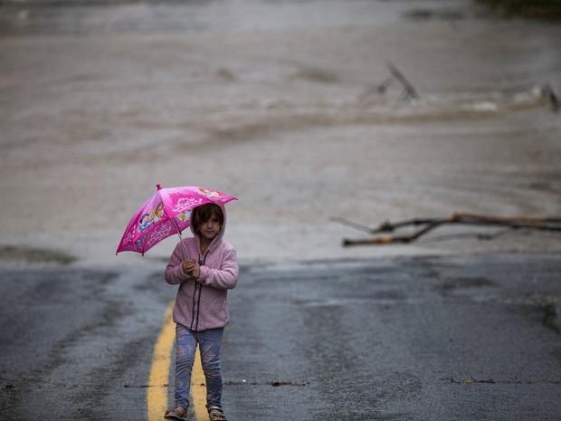 Criança se protege da chuva em meio a alagamento em Austin, Texas, neste sábado (24) (Foto: REUTERS/Adrees Latif)