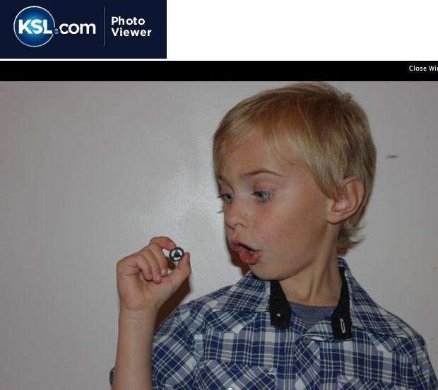 Isaak Lasson, 6 , poa junto com a peça retirada de seu nariz (Foto: Reprodução)