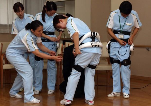 Cuidadores na casa de repouso para idosos Fuyoen experimentam traje robótico Membro de Apoio Híbrido - Hybrid Assistive Limb (HAL) - da Cyberdyne  (Foto: AFP Photo/Yoshikazu Tsuno)