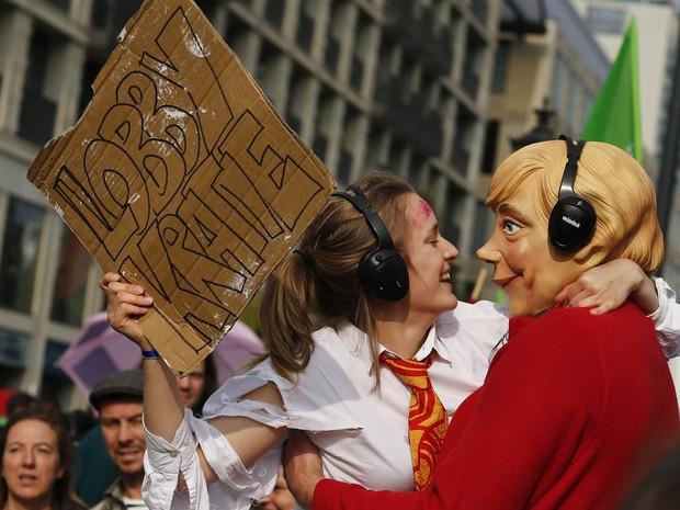Manifestante com um cartaz à mão abraça uma pessoa fantasiada com uma máscara da chanceler alemã, Angela Merkel, durante Marcha Popular pelo Clima em Berlim, na Alemanha (Foto: Thomas Peter/Reuters)