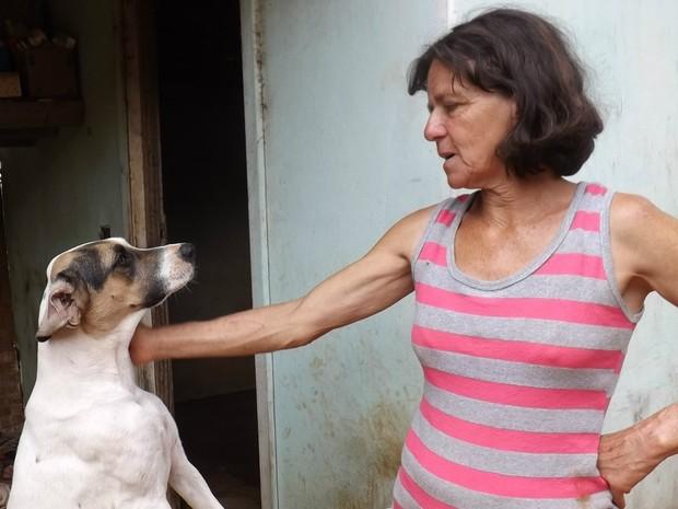 Dona Bene faz carinho em um de seus cães. Além dele há outros 55 (Foto: Caio Silveira/ G1)