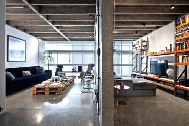 Living. A parede estrutural divide a área social. A sala de estar tem sofá de 3,50 m de largura feito sob encomenda pela Fernando Jaeger Atelier, mesa de centro criada com paletes pelo morador, poltrona do SuperLimão Studio (Foto: Maíra Acayaba / Editora Globo)