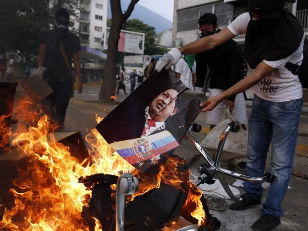 Manifestante queima cartaz com a imagem de Hugo Chávez, depois de saquear um edifício público em Caracas (Foto: Carlos Garcia Rawlins/Reuters)