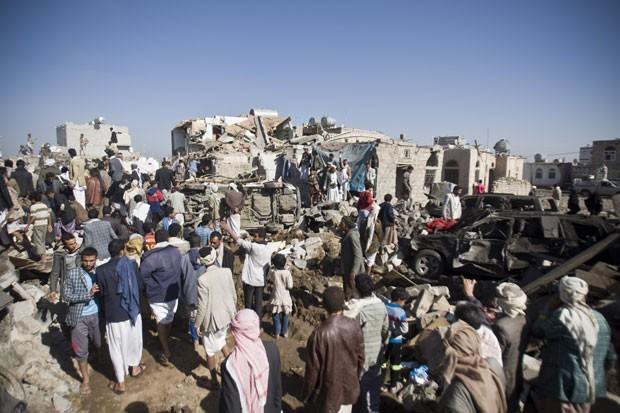 Pessoas buscam por sobreviventes nos destroços de casas atingidas por bombardeio aéreo saudita perto do aeroporto de Sana, no Iêmen, nesta quinta-feira (26) (Foto: Hani Mohammed/AP)