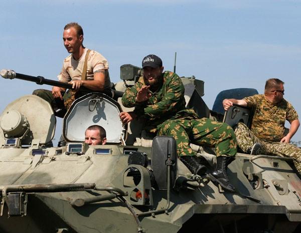 Vestidos com roupas militares, homens em veículos de guerra usam estrada perto da fronteira com a Ucrânia. (Foto: Alexander Demianchuk/Reuters)