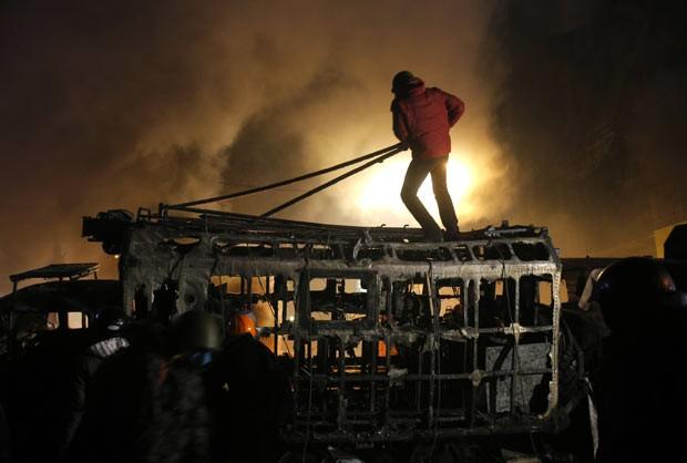Manifestante sobre barricada durante protesto na madrugada desta terça-feira (21) em Kiev, capital da Ucrânia (Foto: Sergei Grits/AP)