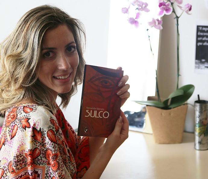 Fernanda mostra a capa de seu primeiro livro (Foto: Gshow)