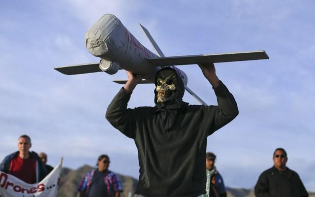 Manifestante mascarado carrega um modelo de drone usado pela Força Aérea nos EUA (Foto: Julie Jacobson/AP)