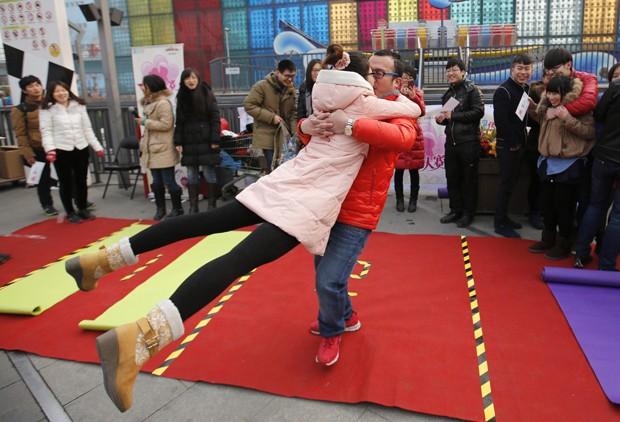 Chinês gira a namorada enquanto dá beijo ao tentar vencer concurso em parque de diversões em Pequim (Foto: Kim Kyung-Hoon/Reuters)