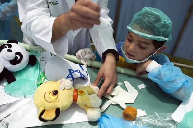 Garoto observa estudante da faculdade de ciências médicas 'operar' um ursinho de pelúcia (Foto: Reuters/Amir Cohen )