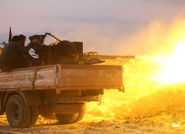 Rebeldes combatem forças do governo com armas pesadas na cidade de Hama, na Síria (Foto: Abu Hadi Al-Hamwi/AFP)