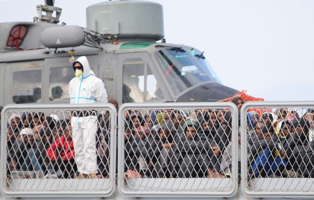Imigrantes resgatados esperam para desembarcar na cidade de Reggio Calabria nesta terça-feira (14) (Foto: Adriana Sapone/AP)