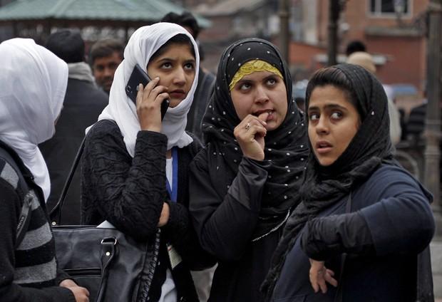 Garotas vão para rua em Srinagar, na Índia, após deixar prédio após terremoto (Foto: Danish Ismail/ Reuters)