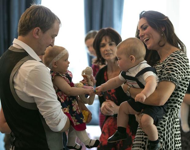 O príncipe George, no colo da mãe, Kate, brinca com outro bebê na Nova Zelândia (Foto: Woolf Crown Copyright/AFP)