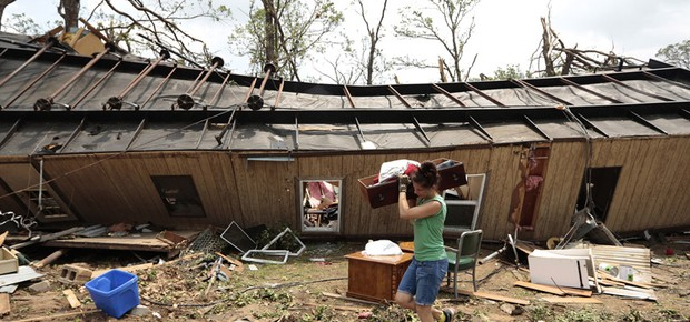 Voluntária ajuda a recolher pertences de uma casa móvel que foi derrubada por um tornado nesta segunda perto de Shawnee, em Oklahoma (EUA). Uma série de tornados atravessam a região central de Oklahoma desde domingo (19) (Foto: Brett Deering/Getty Images)