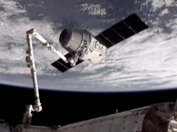A cápsula espacial Dragon, da empresa SpaceX, se acopla à da Estação Espacial Internacional (ISS, na sigla em inglês). A nave foi capturada pelo braço mecânico da ISS às 10h56 (horário de Brasília) e a acoplagem foi concluída às 13h02. (Foto: AP/Nasa)