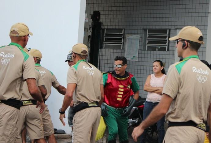 Homem fantasiado tentar pegar na tocha olímpica  (Foto: Josiel Martins)