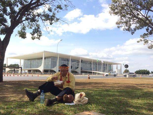 Joel Hilton almoça durante manifestação de indígenas guarani-kaiowá; o grupo pretendia ficar em frente ao Palácio do Planalto, mas foi direcionado pela Polícia Militar a se manifestar em um gramado próximo a Congresso Nacional (Foto: Mateus Vidigal/G1)