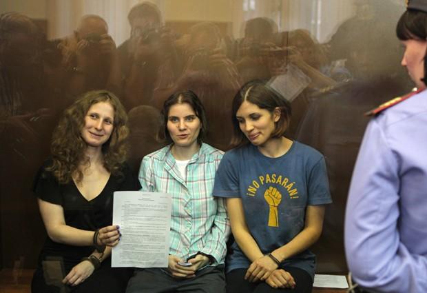 Integrantes da banda punk Pussy Riot seguram o veredito e sorriem. As três foram declaradas culpadas (Foto: Mikhail Metzel/AP)