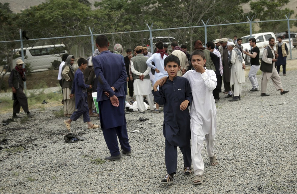 AP Photos/Massoud Hossaini (Foto: Meninos caminham em região de ataque em Cabul, no Afeganistão)