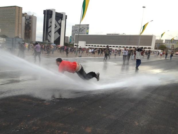 Manifestante é atingido por jato d'água da Polícia Militar diante do Museu da República, em Brasília (Foto: Felipe Néri / G1)