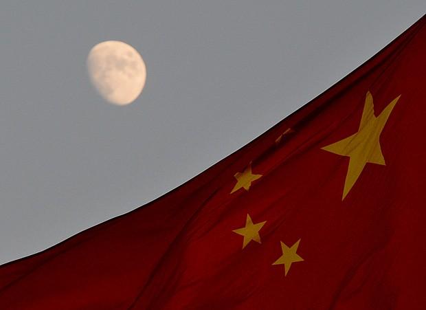 Bandeira chinesa é vista em frente à lua na Praça Tiananmen, em Pequim, nesta sexta-feira (13); veículo lunar chinês deve pousar na Lua neste sábado. (Foto: AFP Photo/Mark Ralston)