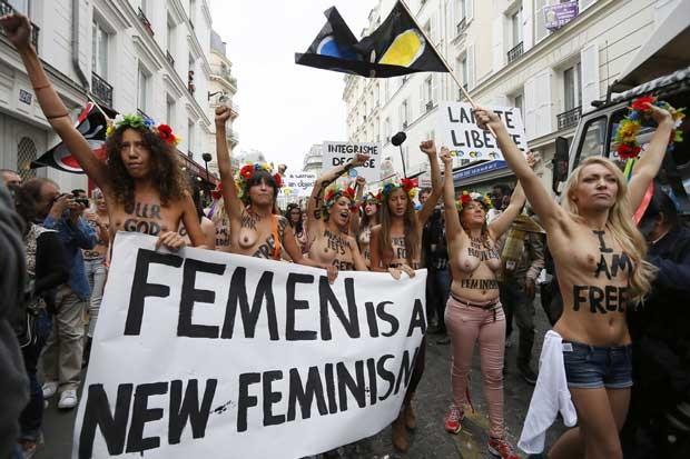 Integrantes seminuas do Femen andam pelas ruas de Paris. O cartaz lê 'Femen é um novo feminismo' (Foto: AFP)