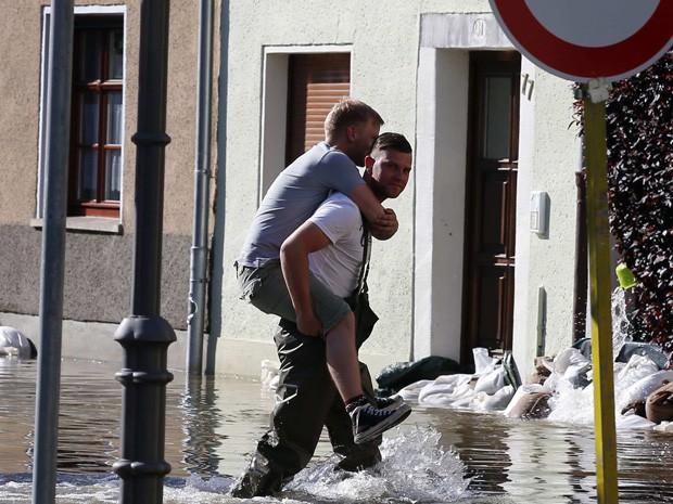 Alemão levou amigo nas costas para enfrentar ruas alagas na cidade de Bernburg (Foto: Tobias Schwarz/Reuters)