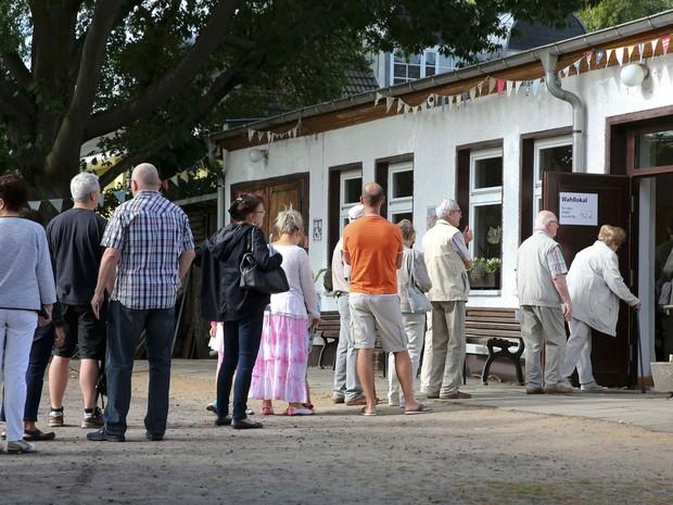 Moradores fazem fila para votar em seção eleitoral de Berlim  (Foto: Fabrizio Bensch/ Reuters)