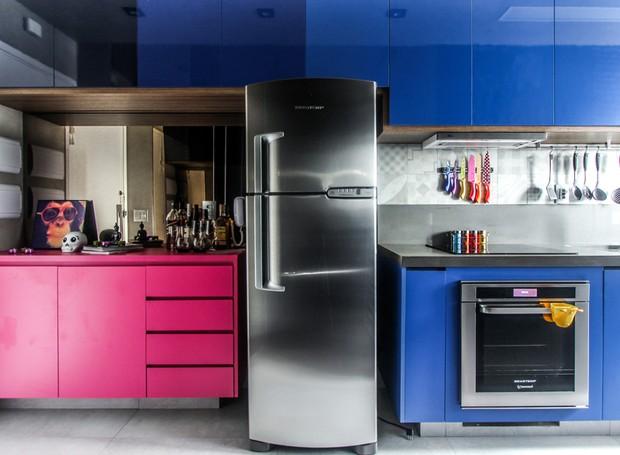 Cozinha | A bancada da cozinha se prolonga desde a porta de entrada do apartamento até a área de serviço. O armário com cores vibrantes, da Dipo Marcenaria, tem função de bar e serve de esconderijo para as máquinas de lavar e secar.  Entre a pia o móvel,  (Foto: André Laiza/Divulgação)