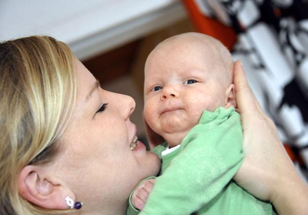 Na França, Dia das Mães começou como incentivo à natalidade; na foto, mãe segura seu filho (Foto: Sari Gustafsson/AFP)