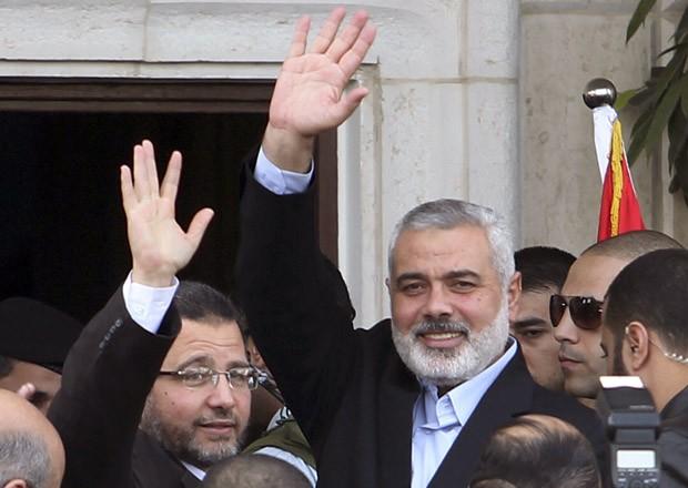 O premiê do Egito, Hisham Kandil, à esquerda, e o líder do Hamas Ismail Haniyeh acenam nesta sexta-feira (16) na cidade de Gaza (Foto: Reuters)