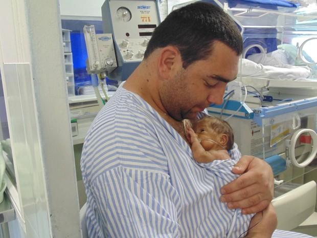 Pai de quadrigêmeas segura uma das filhas no hospital da Unicamp, em Campinas (SP) (Foto: Jaqueline Zanoveli/ G1)