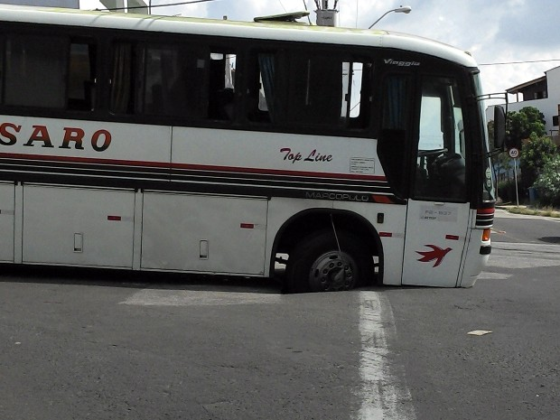 Roda dianteira do ônibus ficou presa no asfalto, que cedeu (Foto: Júlio César Barros/VC no G1)